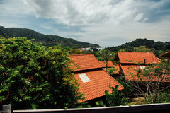 El rojo cubre la casa de planta baja en la colina verde del fondo hermoso y el mar de la costa Imagen de archivo libre de regalías