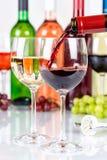 El rojo de colada del formato de retrato de la botella de cristal del vino vierte foto de archivo libre de regalías