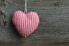 El rojo de la decoración de la Feliz Navidad raya el corazón de la tela Imágenes de archivo libres de regalías