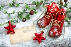 El rojo de la decoración de la Navidad protagoniza la postal antigua de los zapatos de bebé Fotografía de archivo libre de regalías