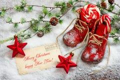 El rojo de la decoración de la Navidad protagoniza y los zapatos de bebé antiguos Fotografía de archivo libre de regalías