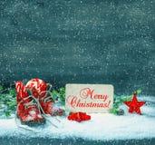 El rojo de la decoración de la Navidad protagoniza y los zapatos de bebé antiguos Fotos de archivo