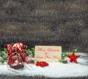 El rojo de la decoración de la Navidad protagoniza y los zapatos de bebé antiguos en nieve Imagen de archivo