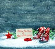 El rojo de la decoración de la Navidad protagoniza y los zapatos de bebé antiguos en nieve Imagen de archivo libre de regalías