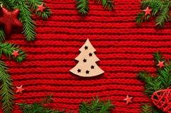 El rojo de la Navidad hizo punto el fondo con el abeto de la rama, las estrellas y el concepto del Año Nuevo del árbol de navidad Imagen de archivo