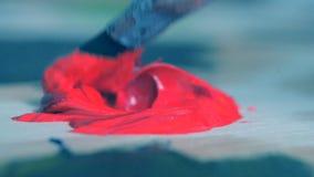 El rojo de la pintura se mezcla con un primer del cepillo almacen de video