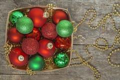 El rojo de las bolas de la Navidad, oro, verde, gotas miente en una cesta de madera t Fotos de archivo