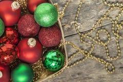 El rojo de las bolas de la Navidad, oro, verde, gotas miente en una cesta de madera t Foto de archivo libre de regalías