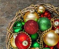 El rojo de las bolas de la Navidad, oro, verde, gotas miente en una cesta de madera t Fotografía de archivo libre de regalías
