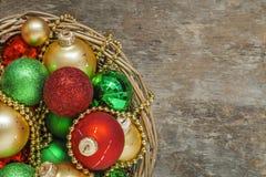 El rojo de las bolas de la Navidad, oro, verde, gotas miente en una cesta de madera t Imagen de archivo