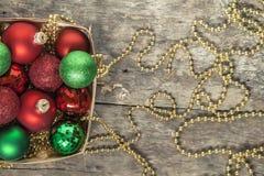 El rojo de las bolas de la Navidad, oro, verde, gotas miente en una cesta de madera t Fotografía de archivo
