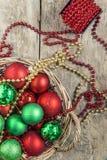 El rojo de las bolas de la Navidad, oro, verde, gotas miente en una cesta de madera t Imagen de archivo libre de regalías