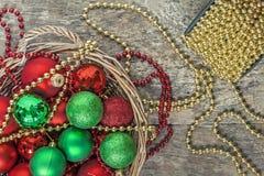 El rojo de las bolas de la Navidad, oro, verde, gotas miente en una cesta de madera t Imágenes de archivo libres de regalías