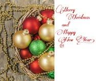 El rojo de las bolas de la Navidad, oro, verde, gotas miente en una cesta de madera w Imagen de archivo libre de regalías