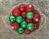 El rojo de las bolas de la Navidad, oro, verde, mentira en un top de madera de la cesta compite Foto de archivo libre de regalías