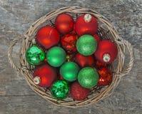 El rojo de las bolas de la Navidad, oro, verde, mentira en un top de madera de la cesta compite Fotos de archivo libres de regalías
