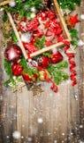 El rojo de las decoraciones de la Navidad protagoniza nieve que cae de los ornamentos de las chucherías Imagenes de archivo