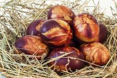El rojo de los huevos de Pascua teñió adornado con las impresiones de las hojas puestas en heno Imagen de archivo