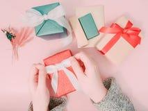 El rojo del abrigo y del paquete de la mano del ` s de la muchacha de la belleza presenta la caja para da y ce Imagen de archivo libre de regalías
