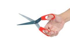 El rojo del uso de la mano del hombre scissor el aislante en el fondo blanco, acortando p Fotos de archivo