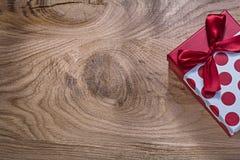 El rojo encajonó el presente de cumpleaños el los días de fiesta c del espacio de la copia del tablero de madera imagenes de archivo