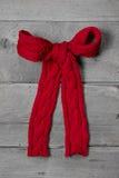 El rojo hizo punto el arco para un presente en el fondo de madera gris - greeti imagen de archivo libre de regalías