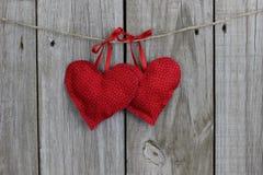 El rojo imprimió los corazones que colgaban por las cintas en clohtesline con el fondo de madera Foto de archivo libre de regalías