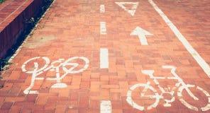 El rojo pavimentó la trayectoria de la bici o una bici se pinta en la pintura blanca Fotos de archivo