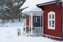 El rojo pintó la casa de madera sueca en un paisaje hivernal imagen de archivo