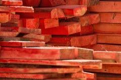 El rojo pintado apiló la pila de madera de las barras en la yarda mater del edificio fotografía de archivo