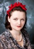 El rojo que desgastaba de la mujer sentía el adorno en el stlyle retro que miraba el aumento Fotografía de archivo libre de regalías