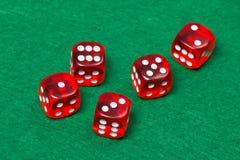 El rojo que juega cinco corta en cuadritos en la tabla verde Imagen de archivo libre de regalías