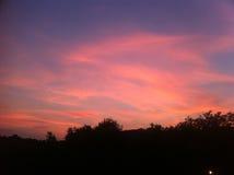 El rojo se nubla el cielo sobre la colina Imagenes de archivo