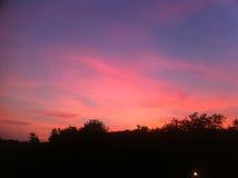 El rojo se nubla el cielo sobre la colina Fotos de archivo