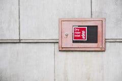 El rojo seco de la caja de la entrada de la canalización vertical en la pared de ladrillo para los servicios de incendios de la e fotografía de archivo