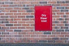 El rojo seco de la caja de la entrada de la canalización vertical en la pared de ladrillo para los servicios de incendios de la e imagen de archivo libre de regalías