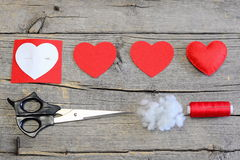 El rojo sentía el corazón, cortar piezas del fieltro en la forma de un corazón, modelo de papel, tijeras, hilo, aguja en una tabl Imagen de archivo libre de regalías