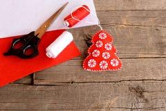 El rojo sentía las hojas de la decoración, de las tijeras, rojas y blancas del árbol de navidad del fieltro, hilo, aguja en fondo Imagen de archivo libre de regalías