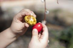 El rojo y el amarillo teñieron los huevos de codornices en manos del ` s de los niños Imagen de archivo