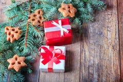 El rojo y el blanco presenta al lado de galletas y de una rama del pino en un fondo de madera Concepto de las compras de la Navid Fotografía de archivo libre de regalías