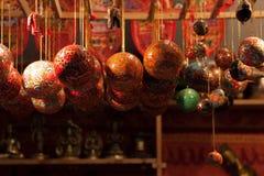 El rojo y el oro colorearon los ornamentos de cristal de la Navidad que colgaban en un quiosco en el mercado de la Navidad - Weih Fotos de archivo