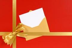 El rojo y el regalo de la Navidad del oro arquean la cinta, tarjeta de felicitaciones en blanco Imagenes de archivo