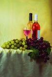 El rojo y el rosé wine, con los manojos de uvas Foto de archivo