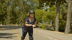El rollerblading femenino joven activo a la velocidad en parque almacen de metraje de vídeo