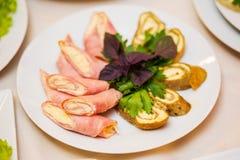 El rollo cortado del jamón relleno con queso sirvió las patatas, hierbas Fotografía de archivo libre de regalías