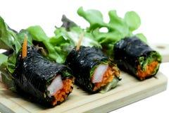 El rollo de la ensalada de la alga marina con las verduras frescas y el cangrejo se pegan en la placa de madera y el fondo blanco fotografía de archivo