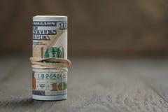 El rollo de los nuevos billetes de dólar del estilo ciento se coloca encendido Imagenes de archivo