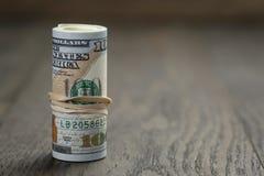 El rollo de los nuevos billetes de dólar del estilo ciento se coloca encendido Foto de archivo libre de regalías