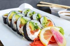 El rollo de sushi con los salmones, aguacate, queso cremoso, puerro, pepino, caviar del tobiko, sirvió en una placa de papel Fotografía de archivo libre de regalías