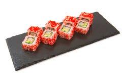 El rollo de sushi con los salmones de los pescados crudos en la comida de la pizarra sube en blanco Comida japonesa Imagen de archivo